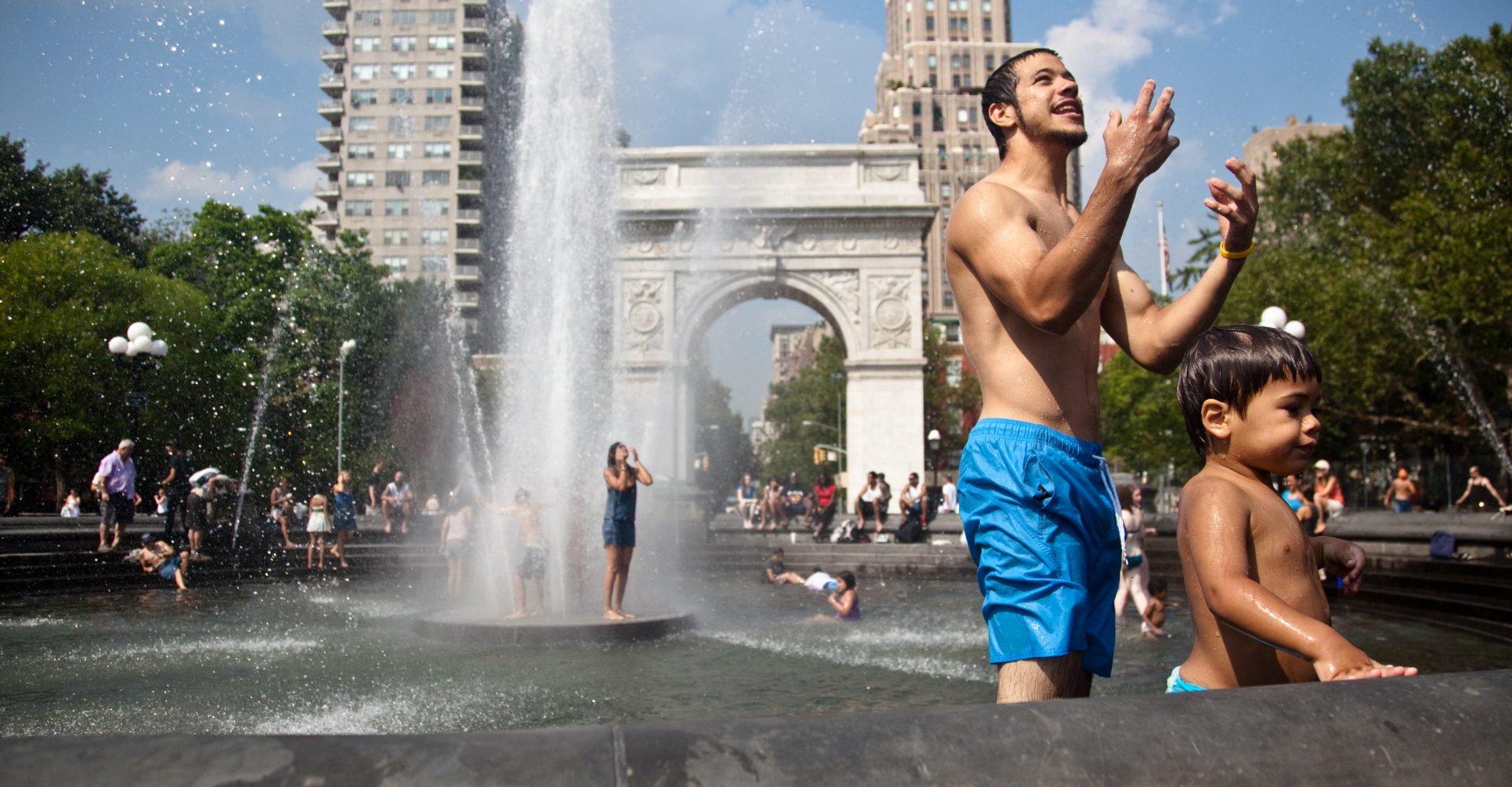 A father helps his son out of the fountain in Washington Square Park as they try to keep cool from yet another east coast heat wave.