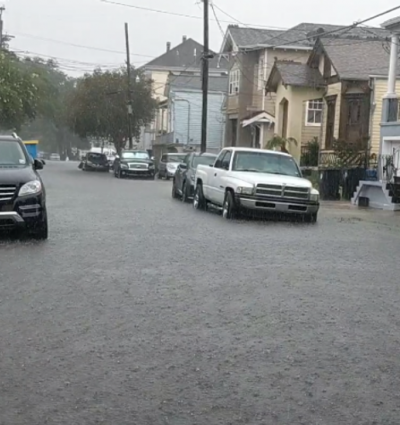 Flooded street with cars in it.